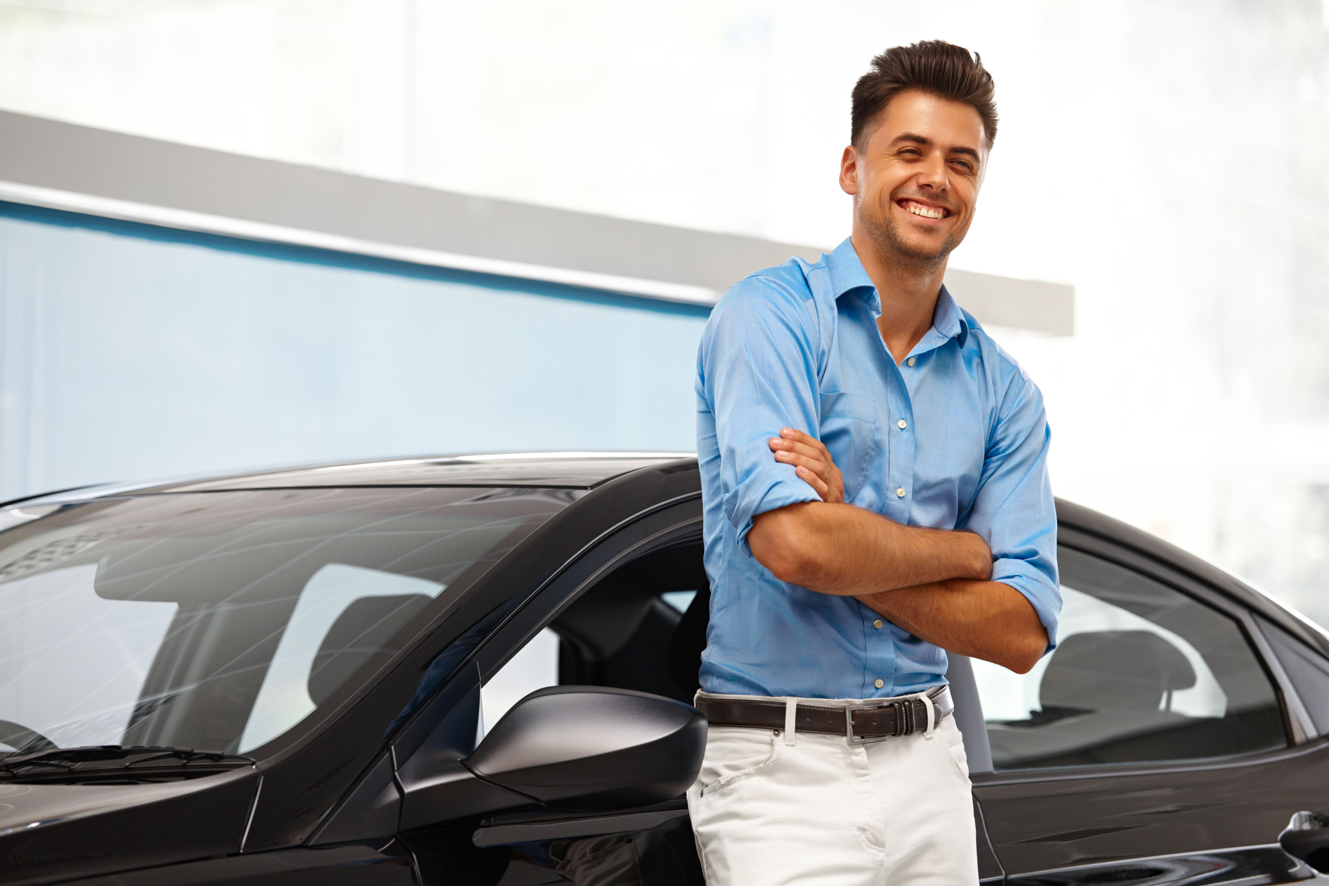 Young Latino man leaning against a new car